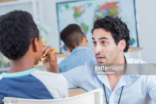 männliche lehrer disziplinen schüler in der klasse - bestrafung stock-fotos und bilder