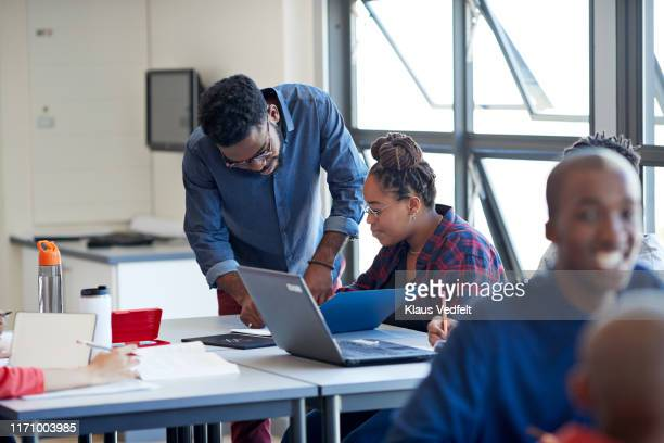 male teacher explaining female student at desk - instructor stock pictures, royalty-free photos & images