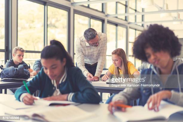 male teacher explaining to multi-ethnic students - classroom stock pictures, royalty-free photos & images