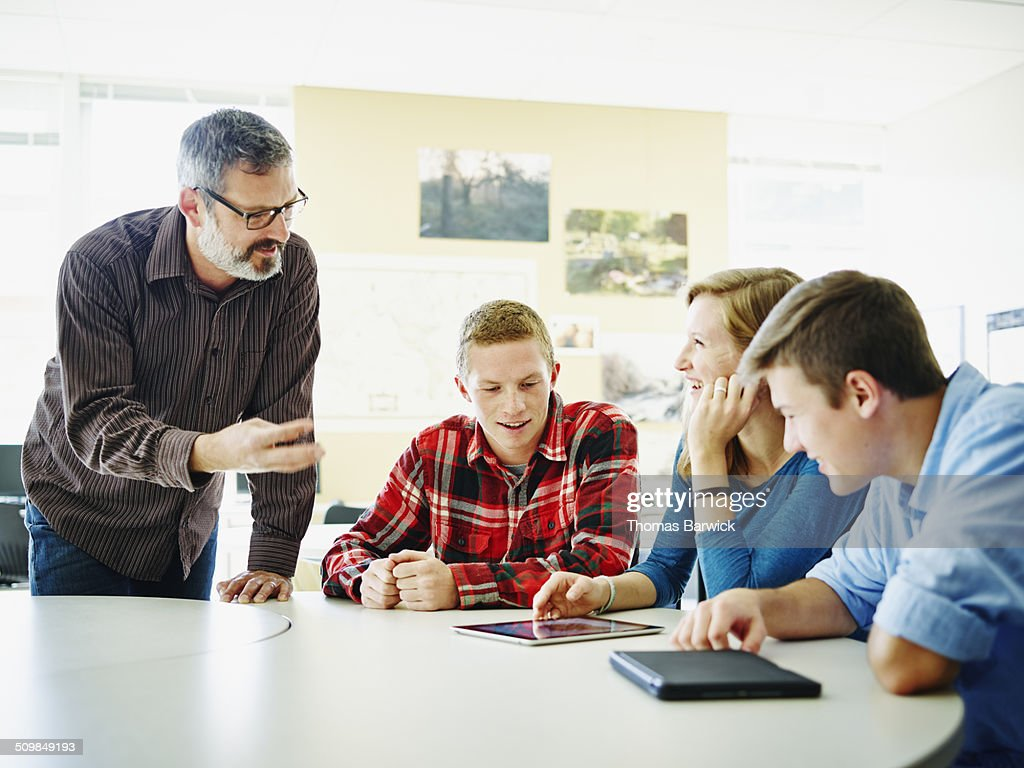 Male teacher helping students work on project : Stock Photo