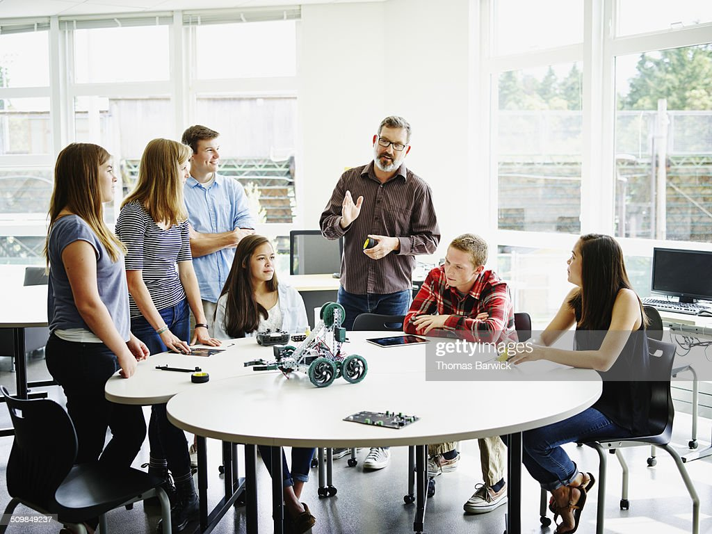 Male teacher in discussion during robotics class : Stock Photo