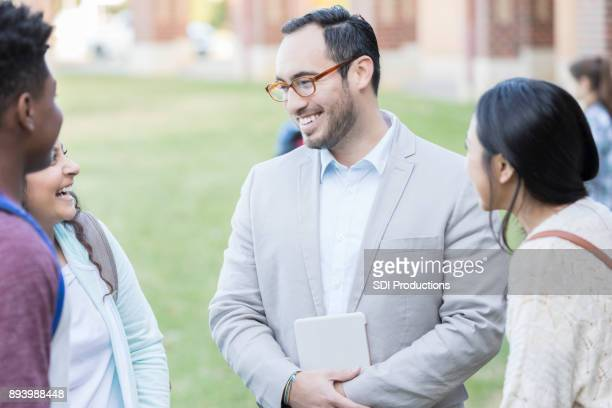 Male teacher or principal talks with group of students
