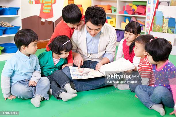 Male teacher reading picture book with cute kindergarten children