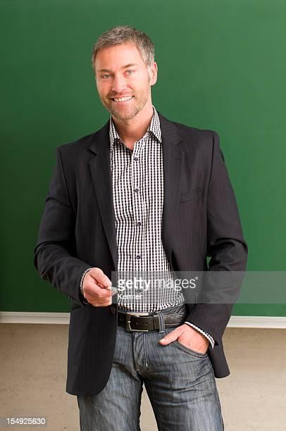 Male teacher smiles in front of blank chalkboard