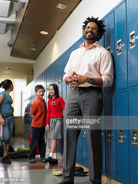 Male teacher standing in hallway with students, portrait