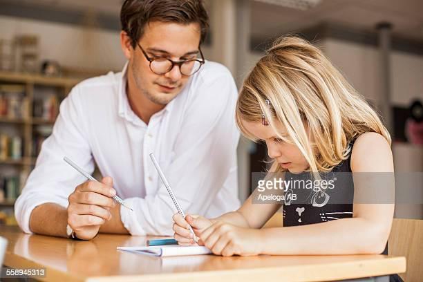 Male teacher teaching girl in classroom