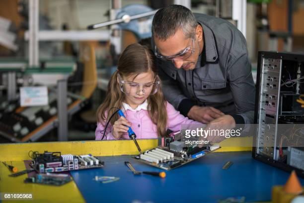 Male teacher teaching little girl how to repair a computer component.