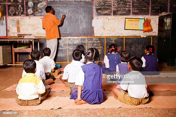 Male Teacher teaching students in a Rural School of India