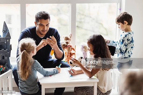 male teacher with students in preschool - preschool building stock pictures, royalty-free photos & images