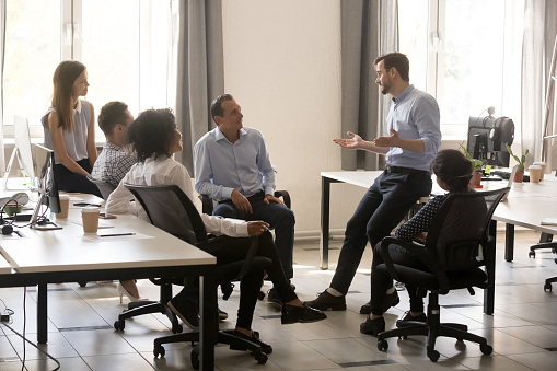 Male team leader talking to diverse businesspeople at office meeting 1070271718