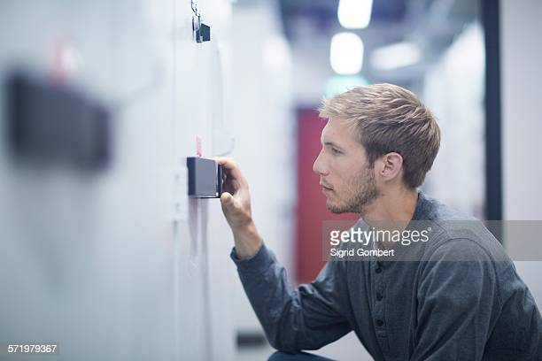 male technician crouching to turn switch in technical room - sigrid gombert stockfoto's en -beelden