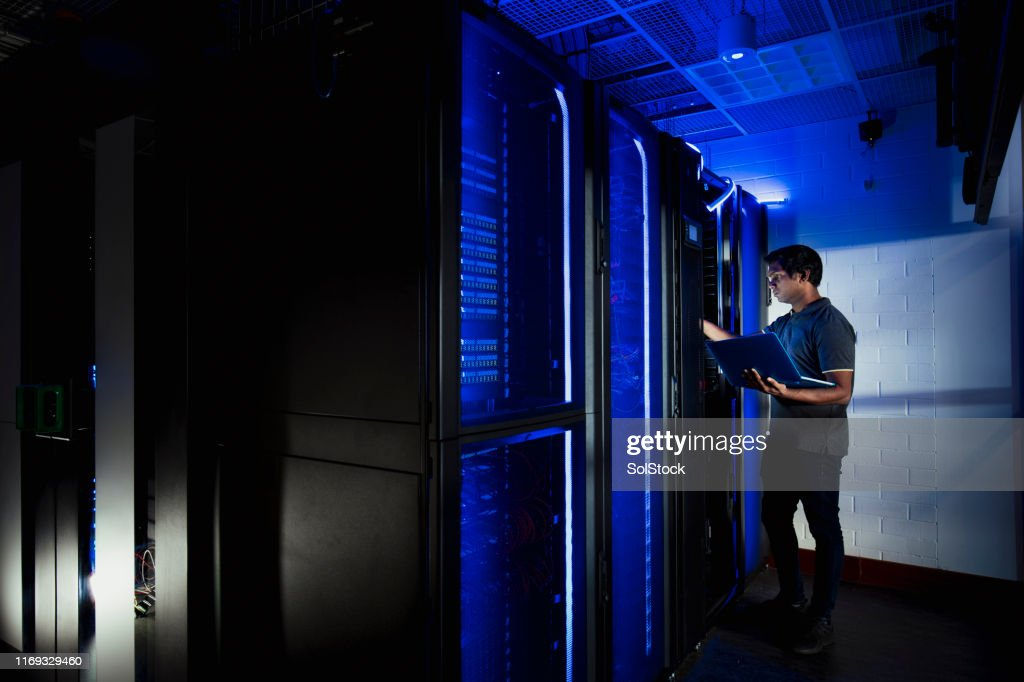 Male Technician Working in Server Room : Stock Photo