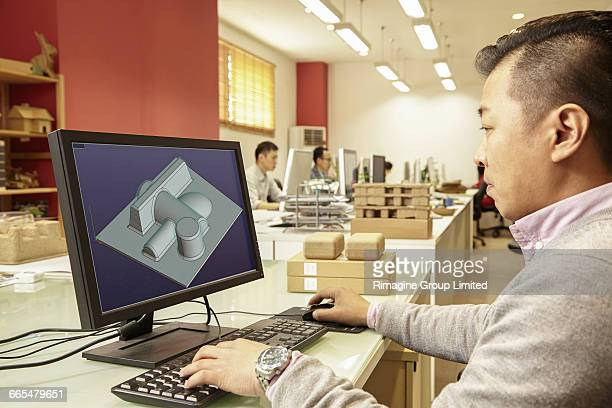 Male technician working on computer in printing and packaging factory, China