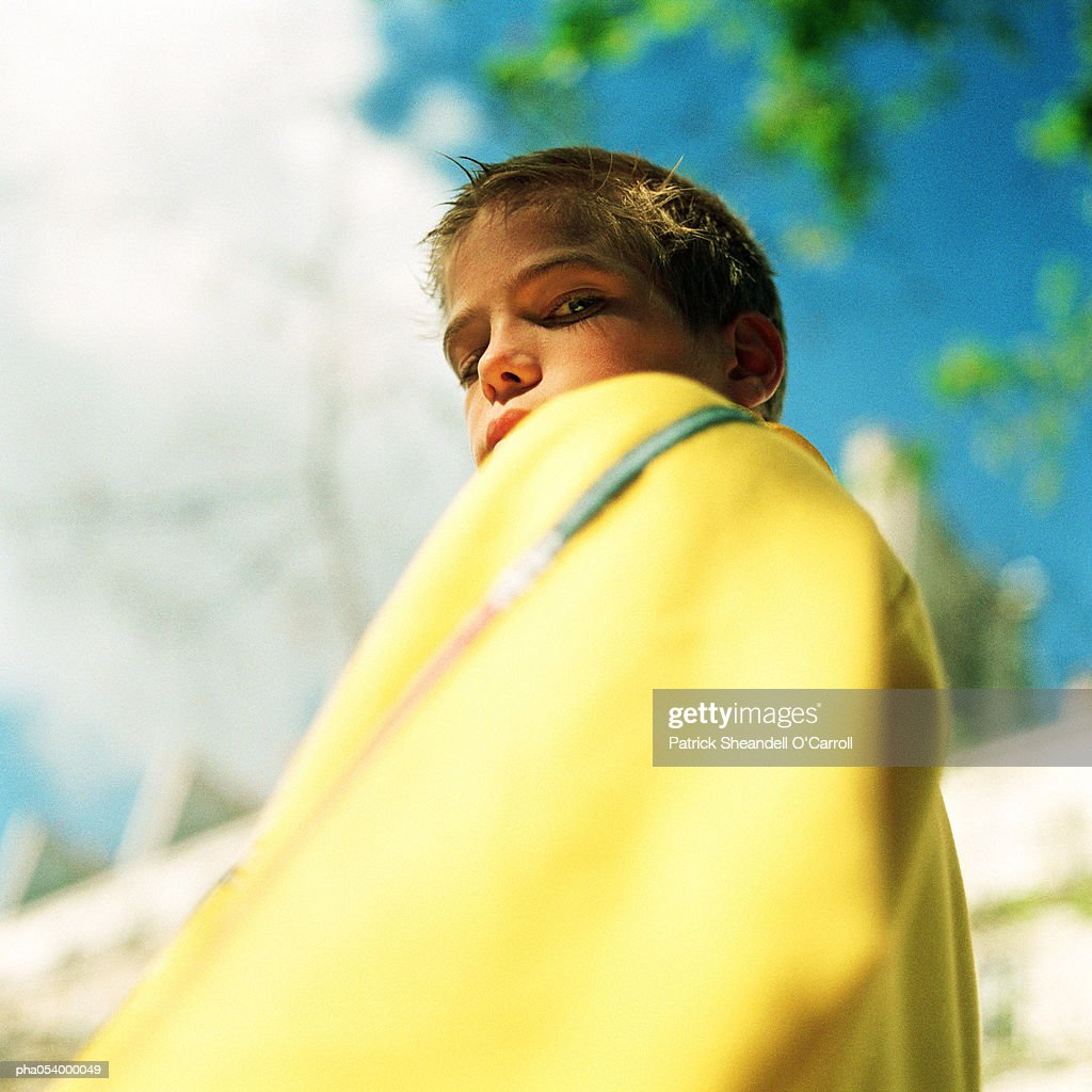 Male teenager covered with yellow blanket looking down into camera : Stockfoto