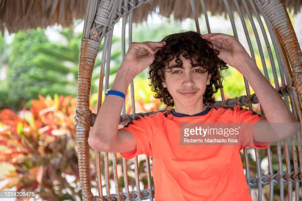 male teenager enjoying a resort garden, cuba - roberto ricciuti foto e immagini stock