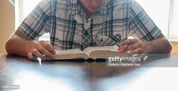 Male teenager reading and studying the Bible or preparing for school by studying his textbook and taking notes