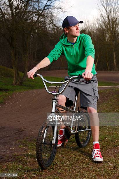 Male teenager relaxes on BMX bike at dirt track