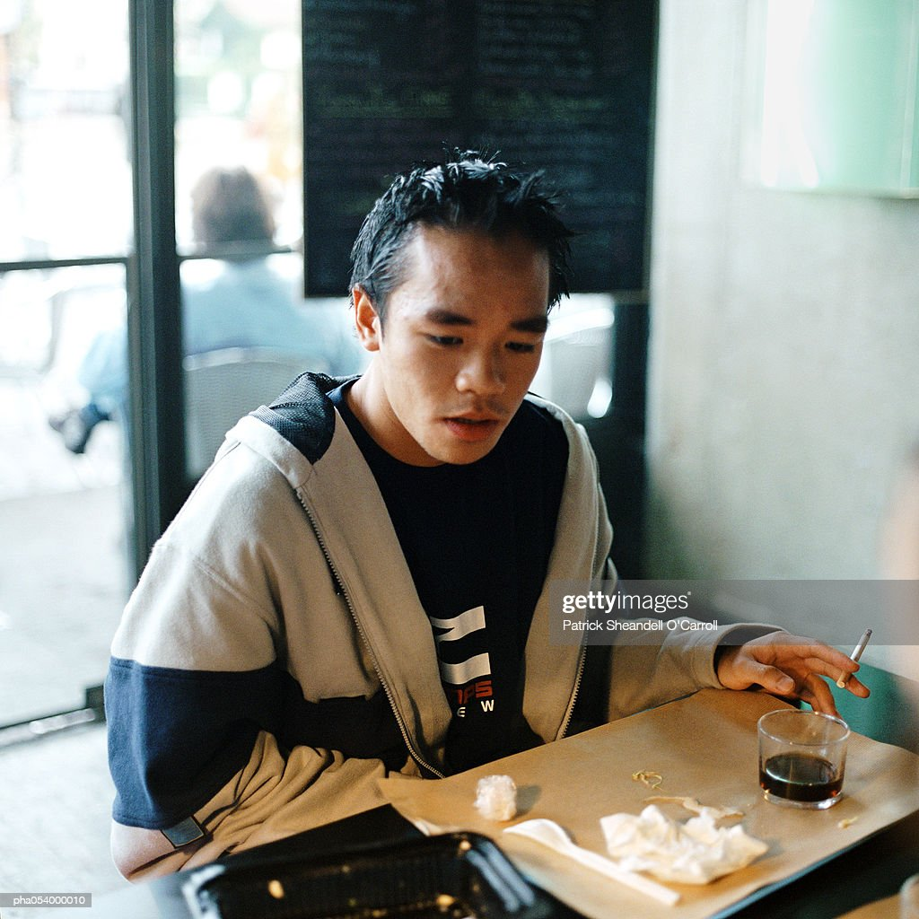 Male teenager smoking at table after a meal : Stockfoto