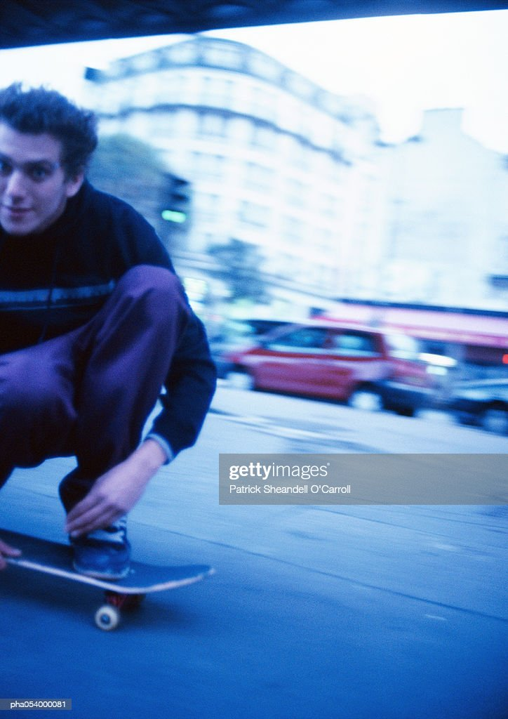 Male teenager squatting on moving skateboard, close-up : Stockfoto