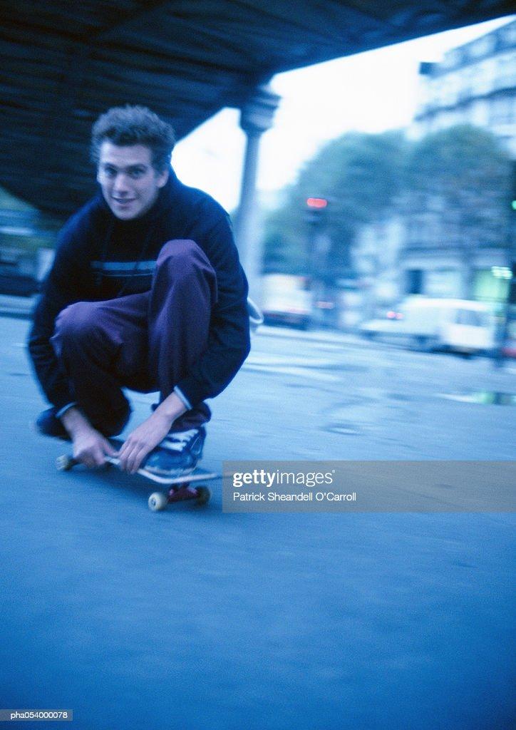 Male teenager squatting on moving skateboard : Stockfoto