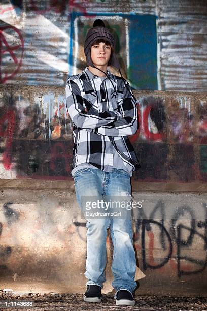 Male Teenager Standing by Graffiti Wall