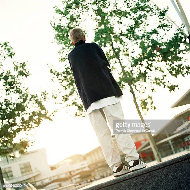 Male teenager standing on platform, rear view