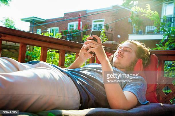 Male teenager using phone lying down on balcony Summer