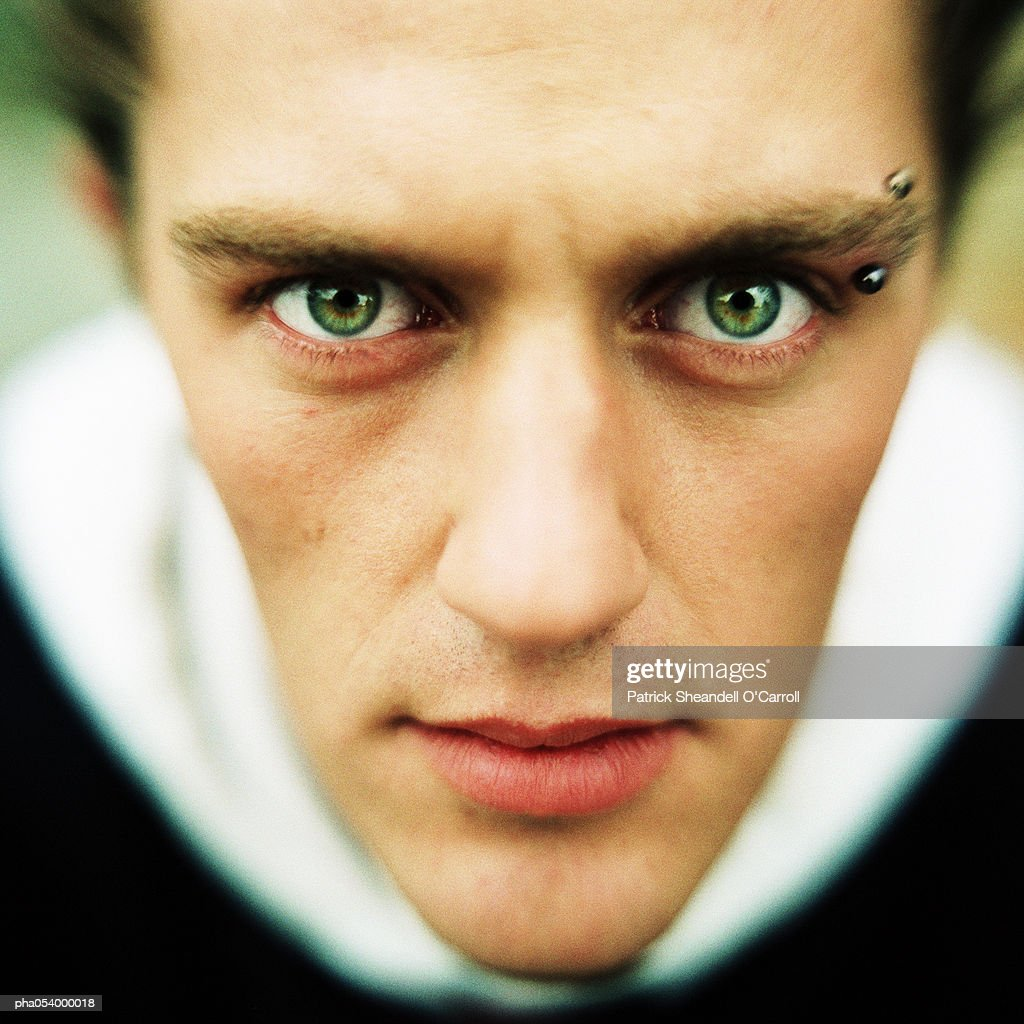 Male Teenager With An Eyebrow Piercing Looking Deeply Into Camera