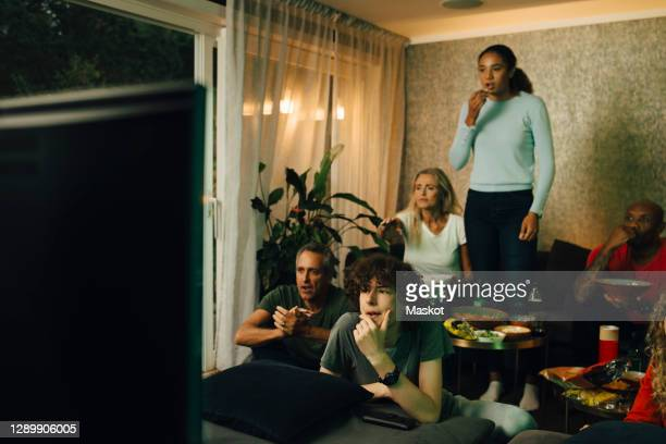male teenager with family by sofa watching tv during sporting event at night - spectator stock pictures, royalty-free photos & images