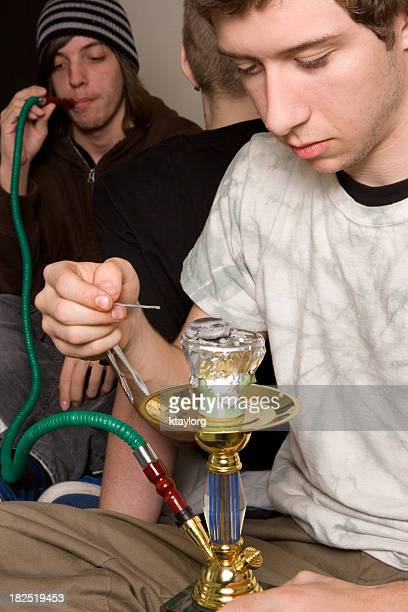 Male teenagers smoking from hookah pipes