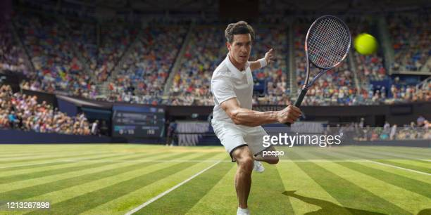 male tennis player about to hit backhand volley in stadium - tennis stock pictures, royalty-free photos & images