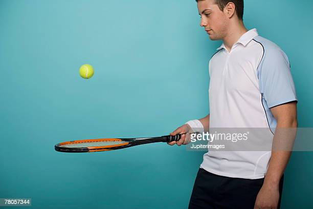 Male tennis player bouncing ball on tennis
