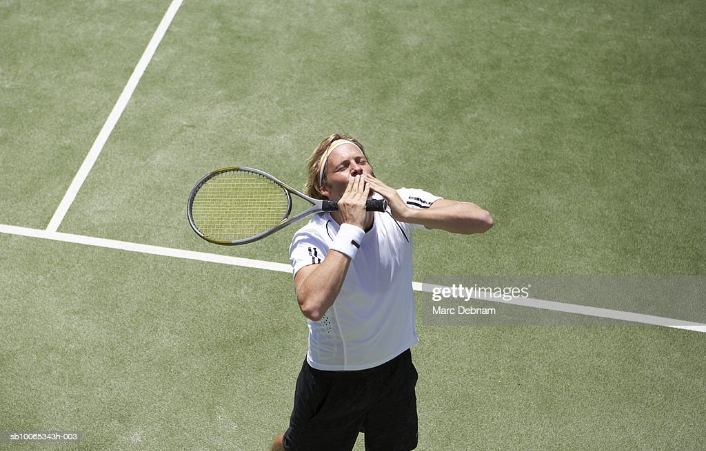 Male tennis player celebrating victory on outdoor court : Foto stock
