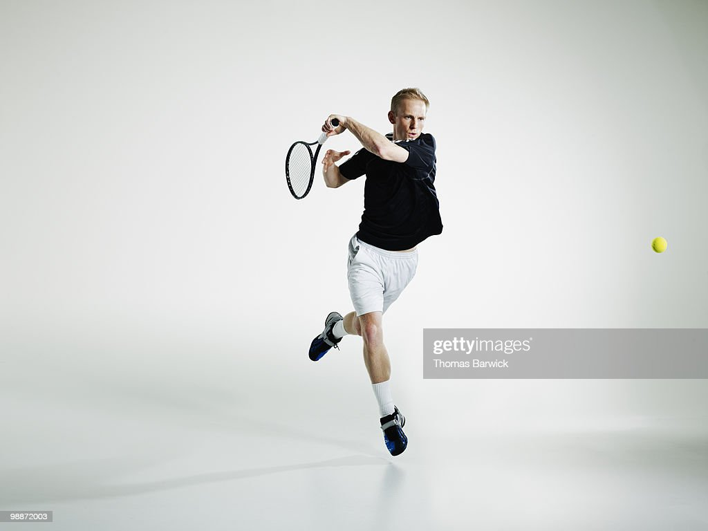 Male tennis player in mid air returning ball : Stockfoto