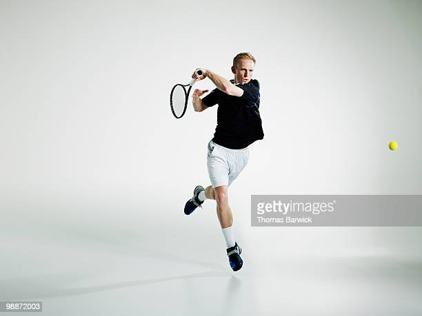 male tennis player in mid air returning ball - tennis stock-fotos und bilder