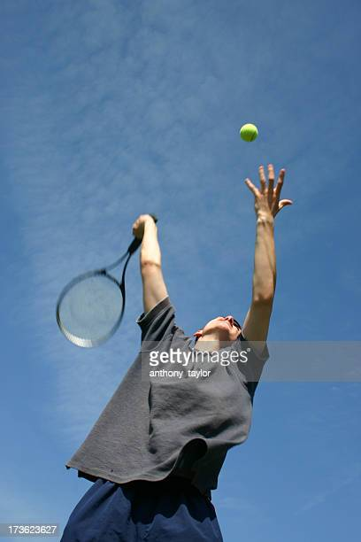 Male tennis player jumping and serving