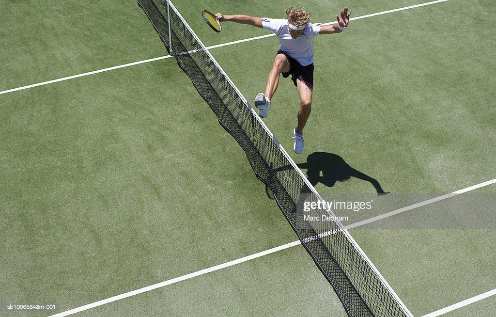 Male tennis player jumping net on outdoor court : Foto stock