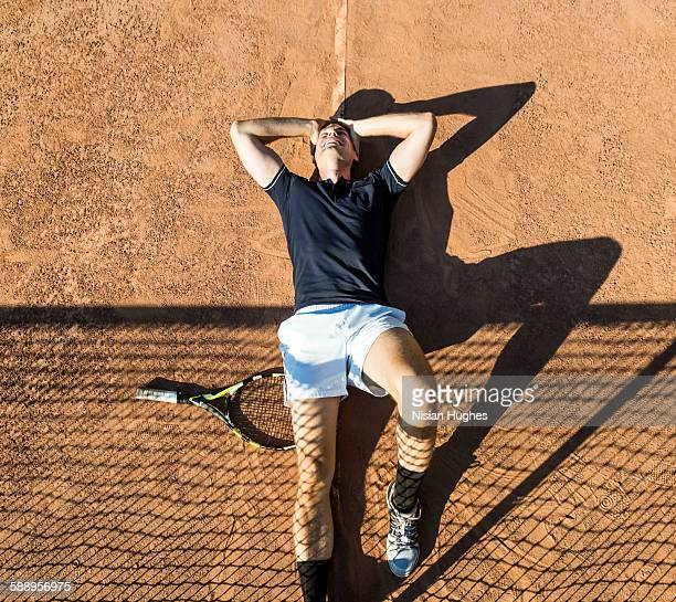 Male tennis player laying on court happy