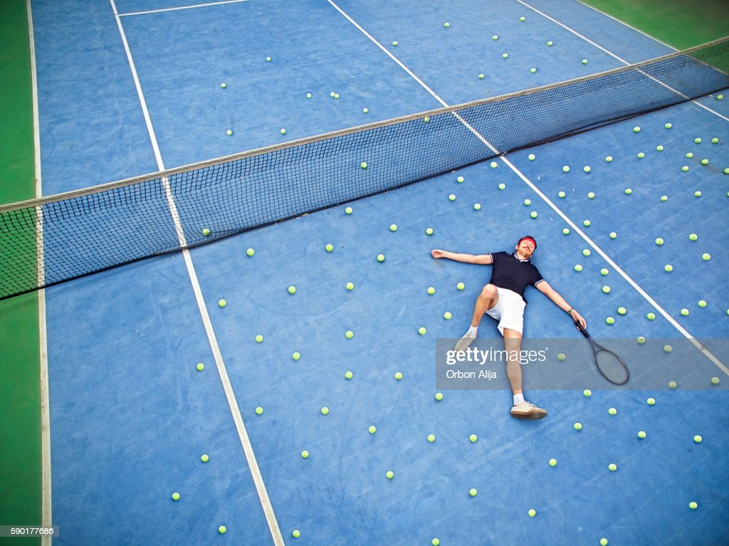 Male tennis player lying on ground : Stock Photo