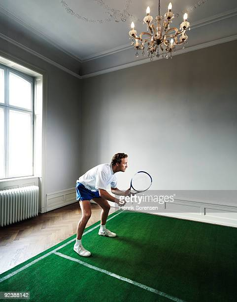 Male tennis player on indoor court in room