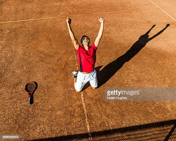 male tennis player on knees celebrating victory