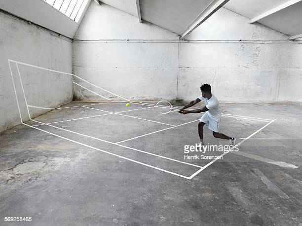 Male tennis player playing on tennis court