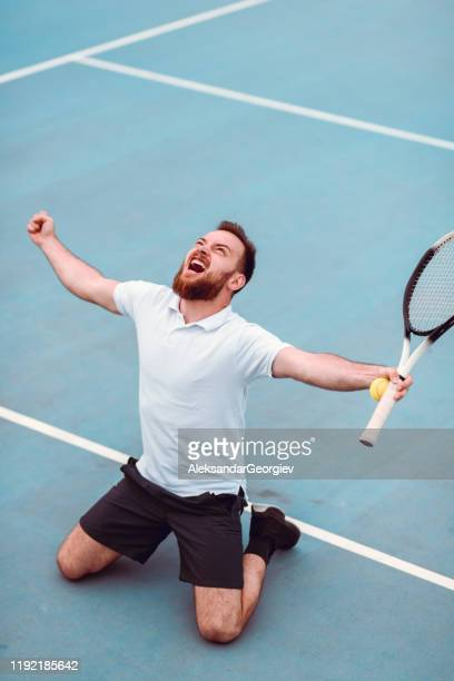 male tennis player roaring after winning match - kneeling stock pictures, royalty-free photos & images