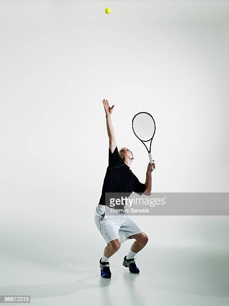 Male tennis player serving ball
