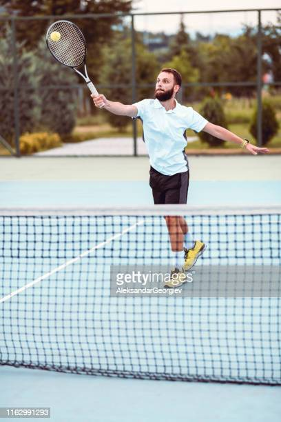 male tennis player struggling to keep up with opponent - tennis player stock pictures, royalty-free photos & images