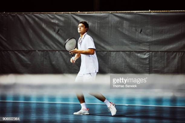 Male tennis player watching shot while playing match on outdoor court at night