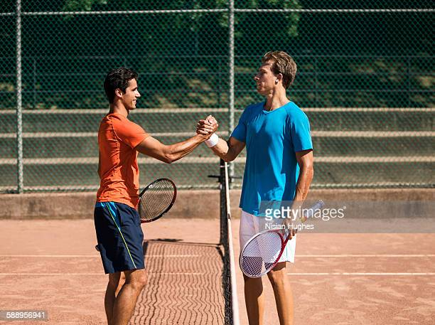 Male tennis players shaking hands after match