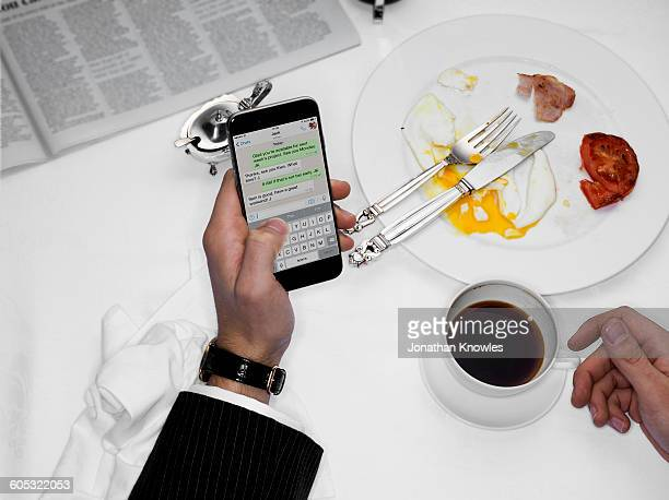 Male texting over finished breakfast