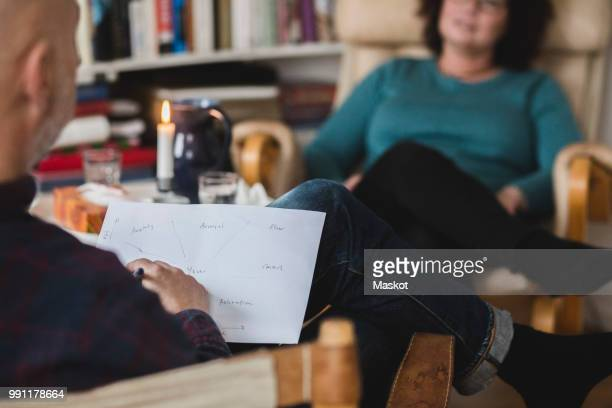 Male therapist analyzing paper while sitting with patient at home office