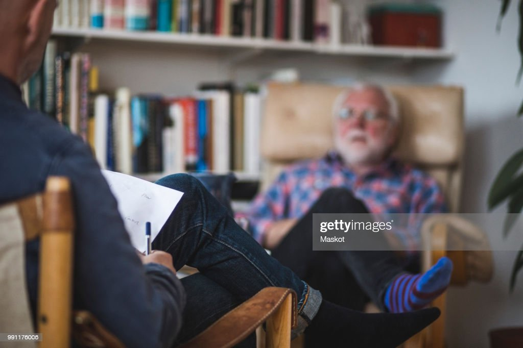 Male therapist with senior patient during therapy session : Stock Photo